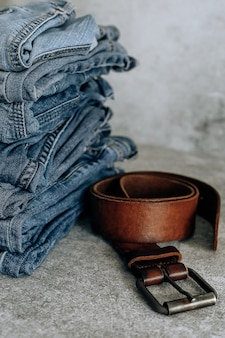 Lot of different blue jeans blue jeans, stack of jeans and brown belt.