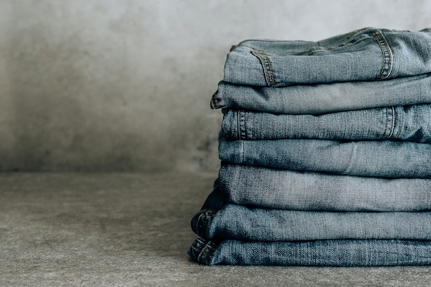 Lot of different blue jeans blue jeans, stack of jeans.