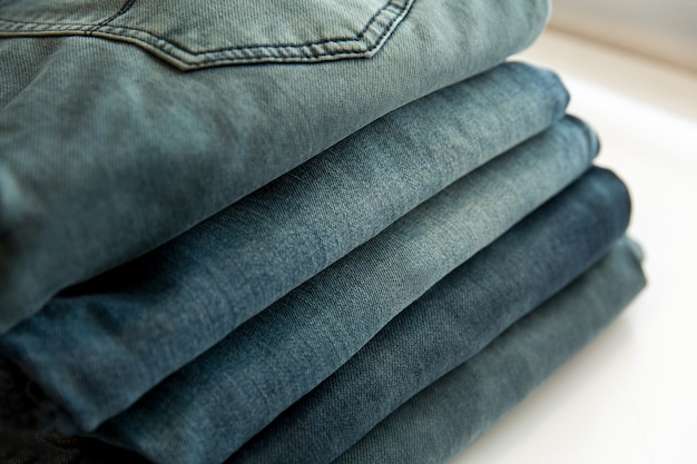A lot of different blue jeans in the shop. denim clothes store