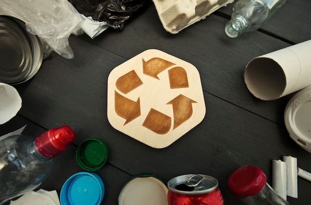 A lot of different garbage on the table and the recycling icon between them