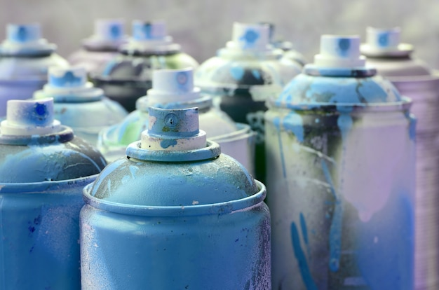 A lot of dirty and used aerosol cans of bright blue paint.