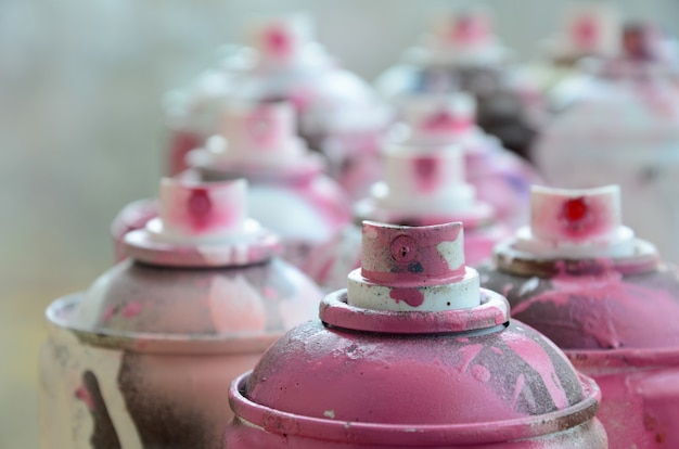A lot of dirty and used aerosol cans of bright pink paint. macro photograph with shallow depth of field.