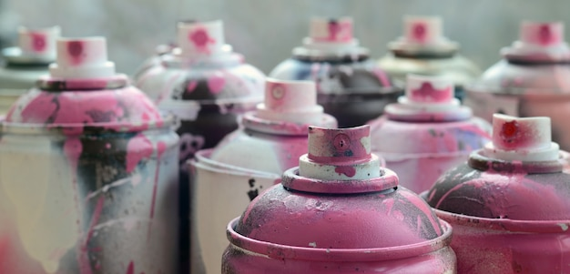 A lot of dirty and used aerosol cans of bright pink paint