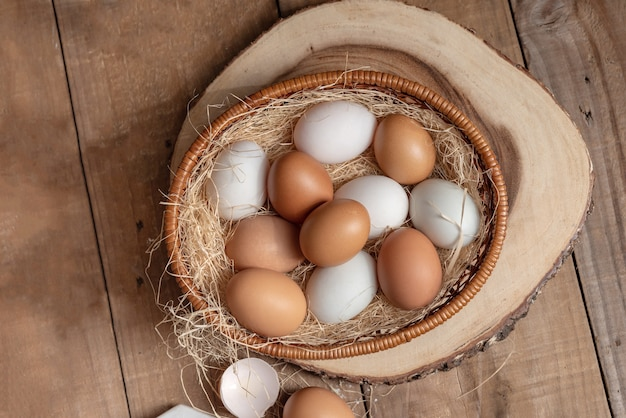A lot of eggs put in the basket and place on the wooden table.