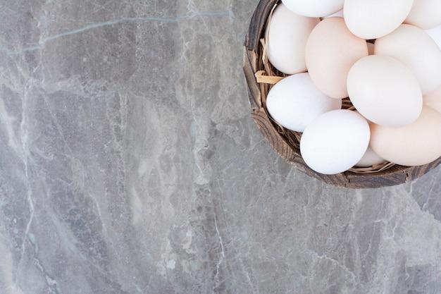 Un sacco di uova bianche di pollo fresco sulla ciotola di legno. foto di alta qualità