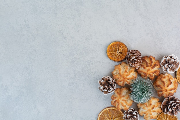 A lot of fresh delicious cookies with small pinecones and dried oranges.