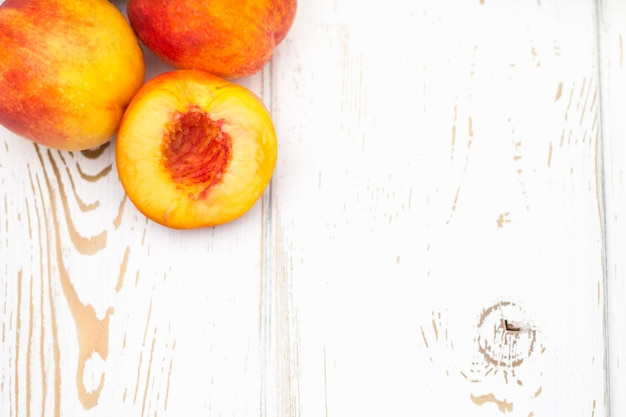 A lot of fresh peaches on a white table. top view.