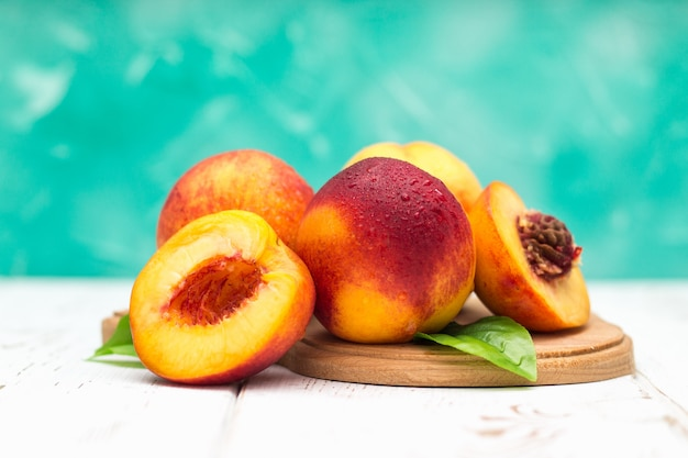 A lot of fresh peaches on a white table.