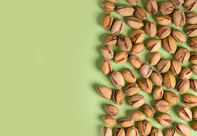A lot of fried pistachios on a green background, top view, flat lay, copy space.