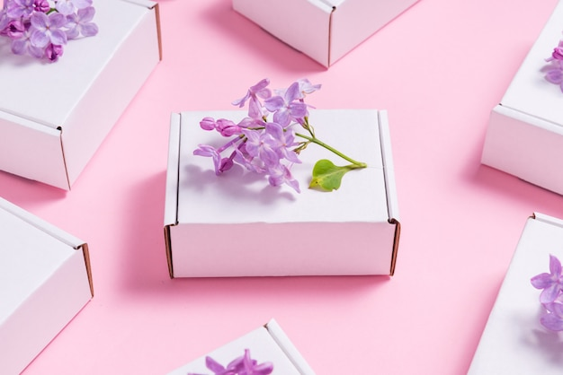 Lot of gift boxes decorated with lilac flowers on pink table