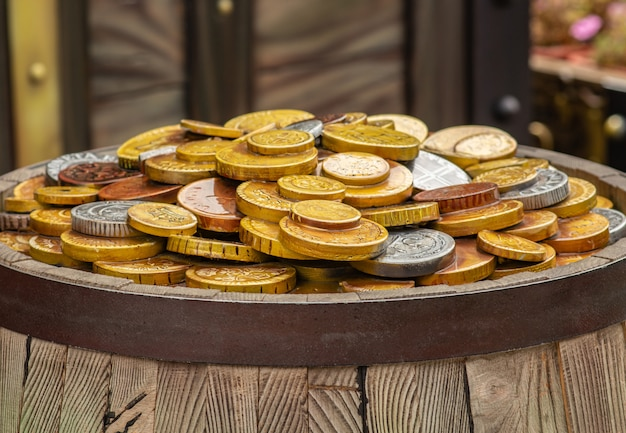 A lot of gold coins on a wooden barrel, the concept of wealth