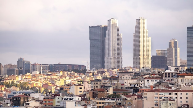 A lot of low residential buildings on the foreground and few skyscrapers at cloudy weather in istanbul, turkey