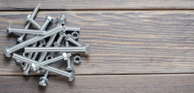 A lot of metal bolts and nuts. tool for fixing. wooden background. copy space