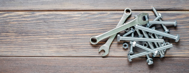 A lot of metal bolts and nuts, a wrench. tool for fixing. wooden background. copy space.