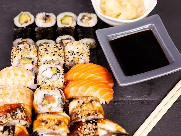 Много разных суши-роллов на черном каменном фоне в студии фото