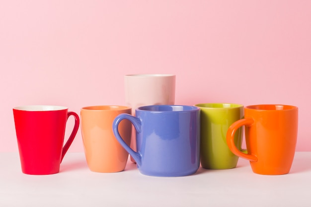 A lot of multicolored cups of coffee or tea on a pink background. the concept of a friendly company, a large family, meeting friends for a cup of tea or coffee.