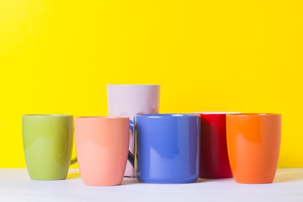 A lot of multicolored cups of coffee or tea on a yellow background. the concept of a friendly company, a large family, meeting friends for a cup of tea or coffee.