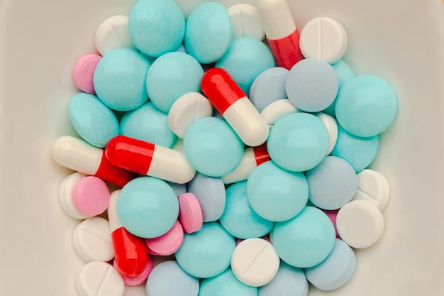 A lot of multicolored pills and capsules on white background as a concept of addiction from medicine