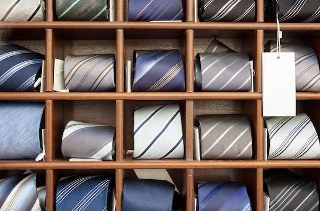 A lot of new ties in the wooden box exposed in a clothes shop
