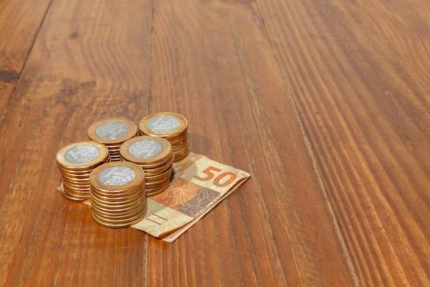 Много бразильских монет и банкнот на деревянном столе