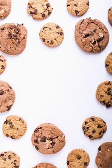 コピースペースのある白い背景の上に円形に配置されたたくさんのチョコレートチップクッキー