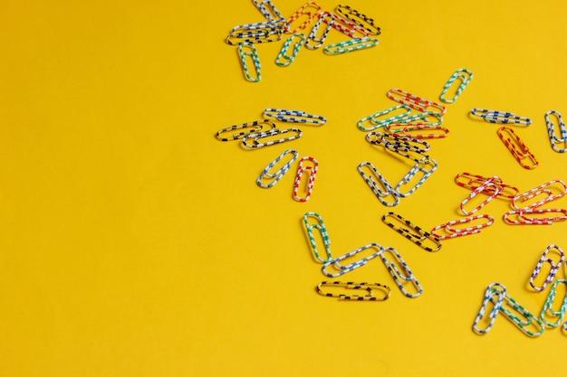 黄色の背景に色付きのペーパークリップがたくさん。ミニマルなオフィスコンセプト。