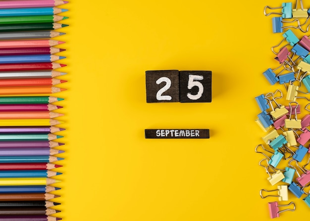 9月25日の木製カレンダーの日付と黄色の背景に色鉛筆がたくさん