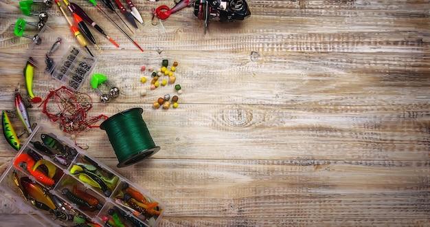 Много красочных приманок с удочкой на деревянной пристани