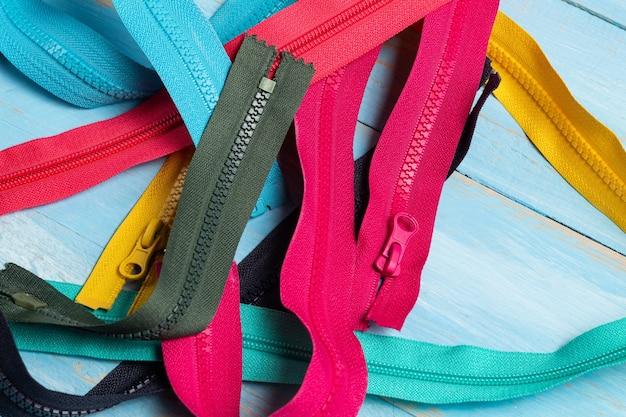 슬라이더가있는 다채로운 플라스틱 및 금속 지퍼 줄무늬가 많이 있습니다.
