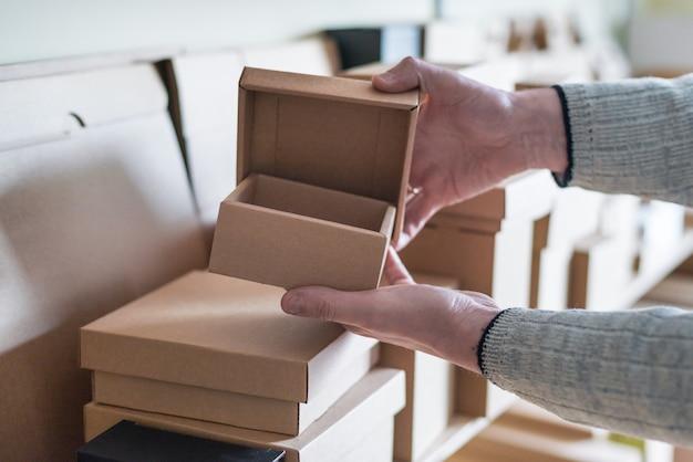 倉庫にはさまざまな段ボール箱がたくさんあります。男の手がボックスを取る