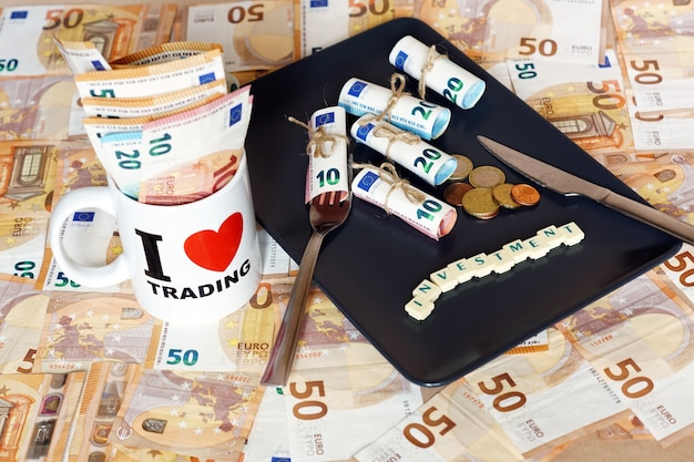 Много денежных купюр dinero в тарелке с ножом, вилкой и чашкой с любовным торговым знаком