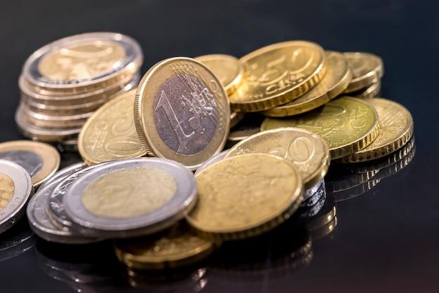 黒いテーブルに反射したユーロ硬貨がたくさん。