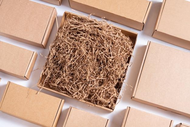 종이 필러가 있는 평평한 갈색 판지 상자가 많이 있습니다.