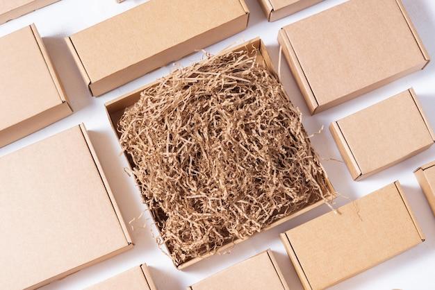Много плоских коричневых картонных коробок с бумажным наполнителем