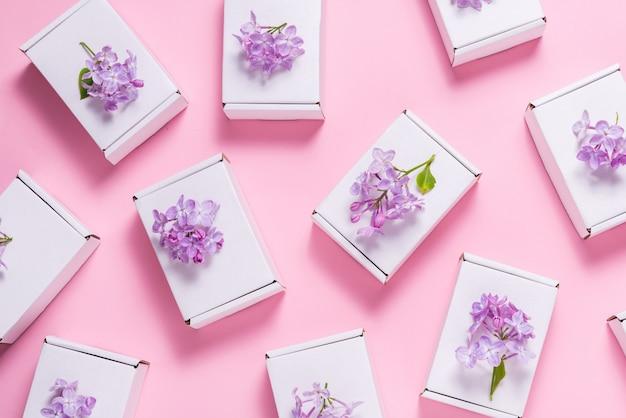 ピンクの背景にライラックの花で飾られた多くのギフトボックス