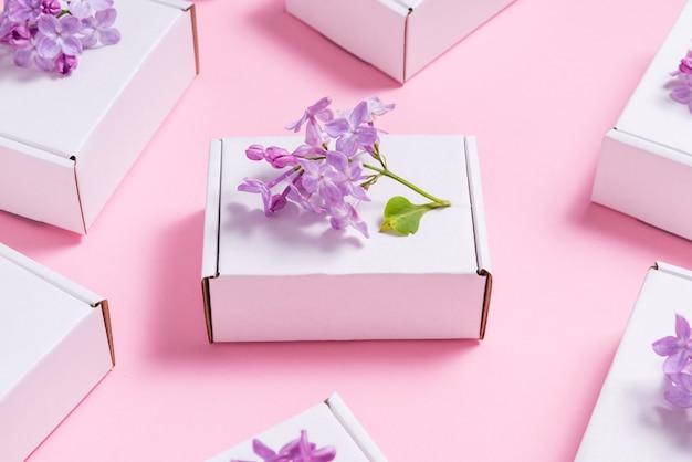 ピンクのテーブルにライラックの花で飾られた多くのギフトボックス