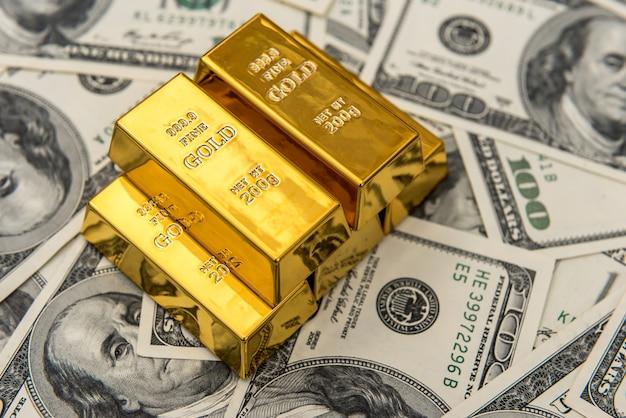 Много золотых слитков на долларовых купюрах. сэкономить деньги концепции. сокровище