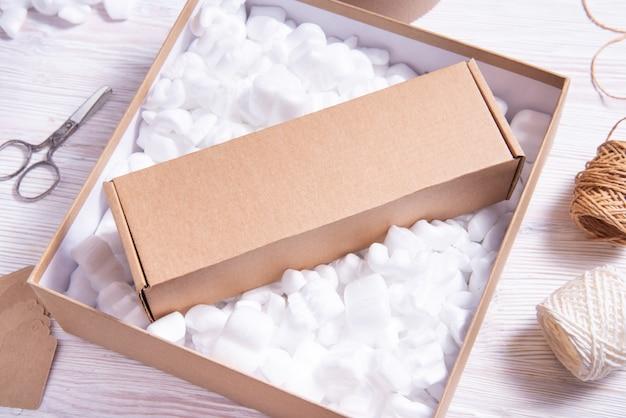 段ボール箱にたくさんのゆるい白いフィラー輸送パッキングピーナッツ