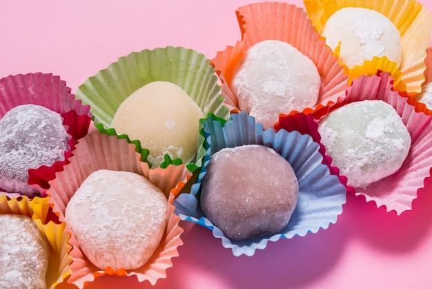 Много десертов моти в бумажных стаканчиках на розовом столе