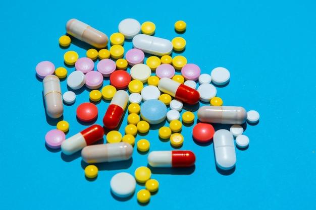 処方箋による治療の概念として青い背景に色とりどりの丸薬がたくさん