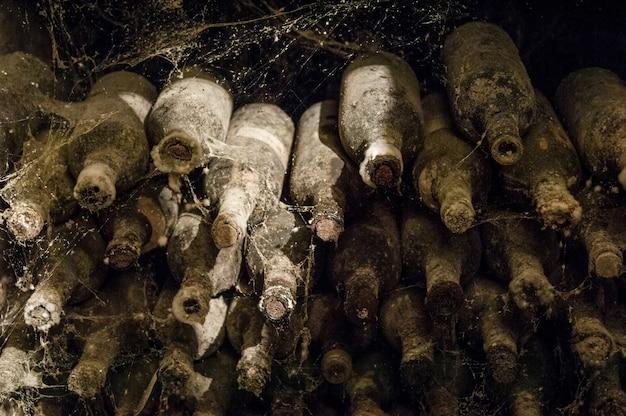 ワインセラーのクローズアップの蜘蛛の巣にたくさんの古いワインボトル