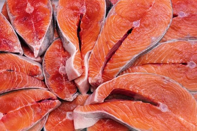많은 조각의 원시 태평양 붉은 생선 치누크 연어를 스테이크로 자르고 다양한 맛있는 요리를 요리할 준비가 되었습니다. 신선한 야생 물고기 king salmon의 클로즈업 평면 레이아웃 - 진미 아시아 요리.