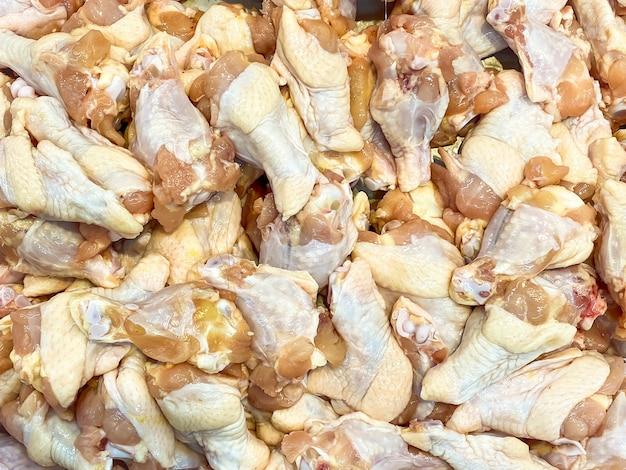 Много сырых куриных крылышек в лотке для продажи в супермаркете