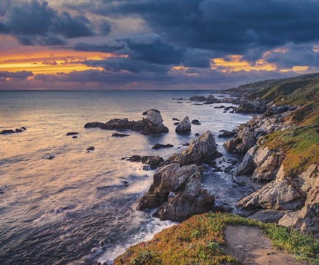 夕焼け空の下、海の近くの苔で覆われた岩の多く