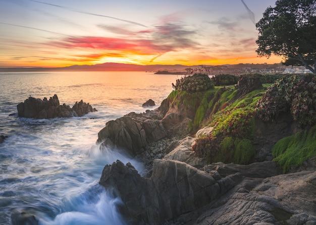 夕焼け空の下で海の近くの苔で覆われた岩の多く