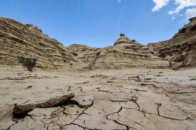 澄んだ青い空の下のバッドランズのたくさんの岩層