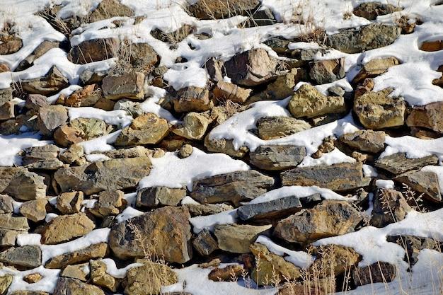 다양한 크기의 바위가 눈으로 덮여 있습니다.