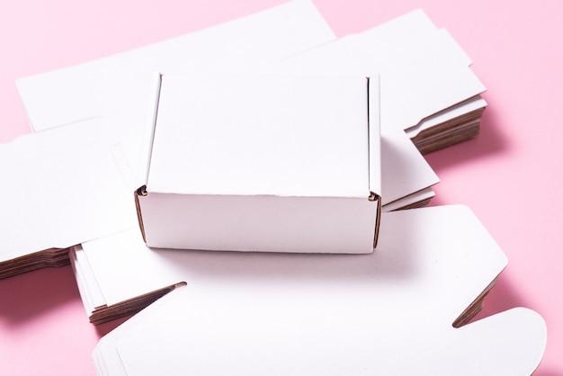 ピンクの背景、刈り取らの多くの正方形のカートンボックス
