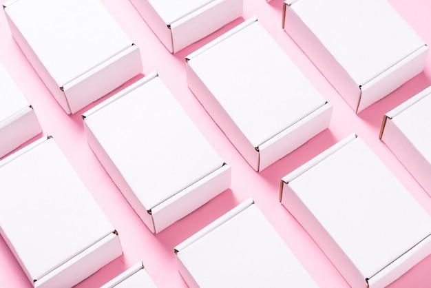 ピンクの背景の正方形のカートンボックスがたくさん