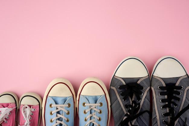 Много текстильных изношенных кроссовок разных размеров